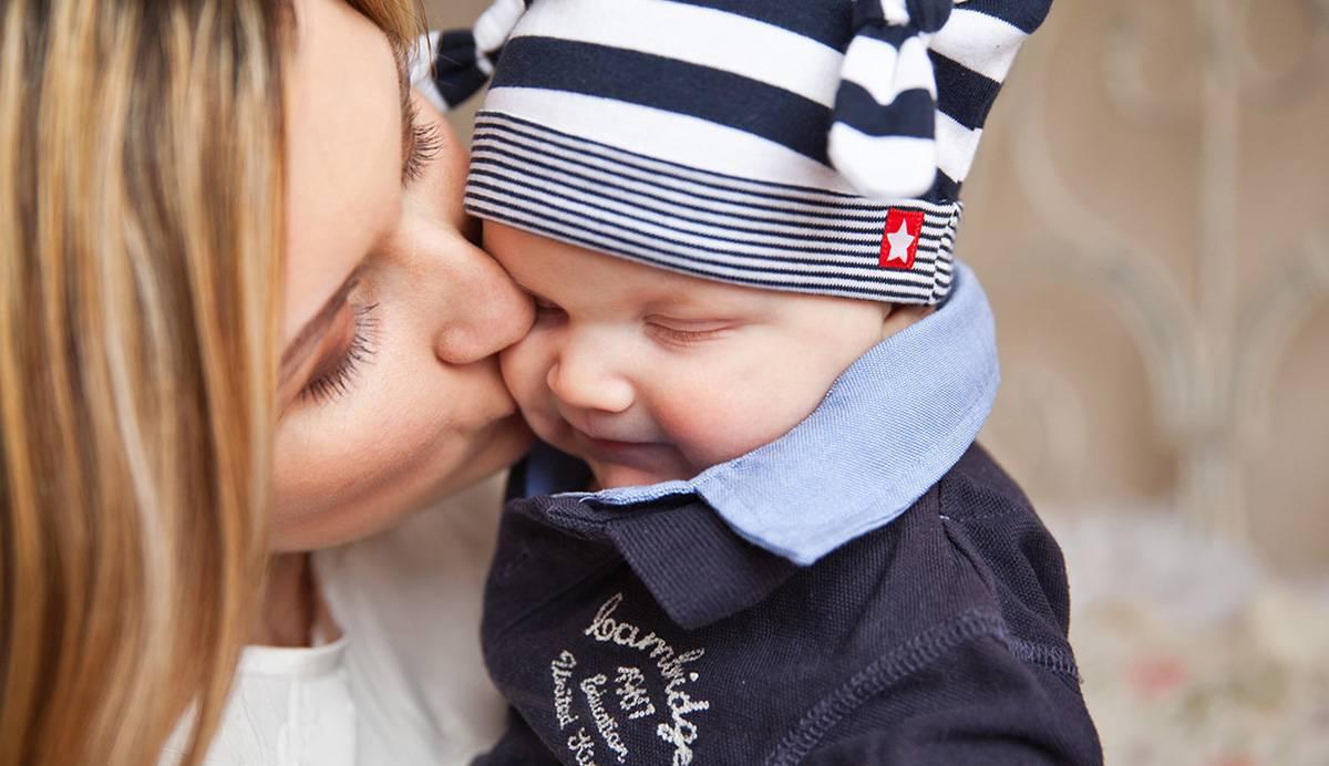 fotografía de una madre besando a su bebé